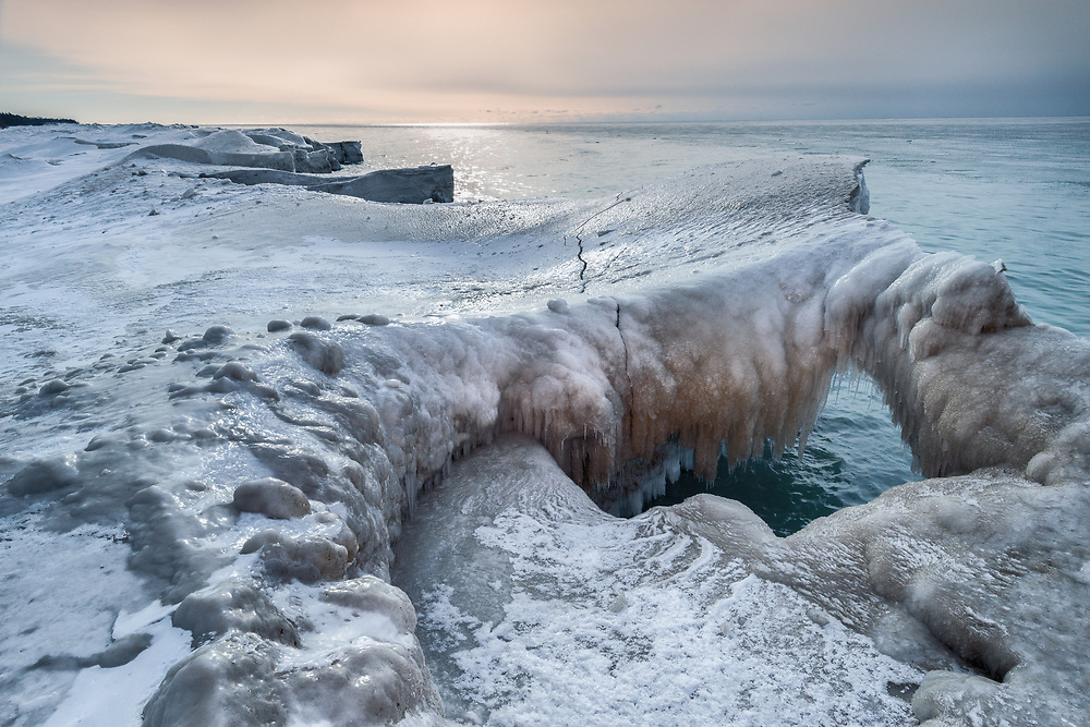The photographs in this series entitled: Ontario Ice Arch, Volcano on Ice, Icing Triangular, Shoreline Ice and Icing Pyramids where made on two separate visits to the shoreline of Lake Ontario in 2014. From 2010 to 2015, I travelled and photographed along the Canadian side of the Lake Ontario Shoreline. The goal was to photograph the development, degradation and beauty found on a variety of sites. In the winter of 2014 in Northumberland County the ice conditions along the shoreline were absolutely spectacular. Extremely cold weather created an above average freeze up on the Great Lakes. The five photographs shown in this series were taken during February and early March, either in the early morning or late daylight. As I walked out onto the ice flow with cleats I found a world of shapes and elegant beauty. I was transported to an Arctic environment, one of sculptured ice and snow. I spent many joyful hours out on the ice, amongst the bitter cold, alone and connected to the lake in a spiritual way. Little did I know that this 2014 display of ice would not easily be repeated if ever because of climate change? Every year since 2014 there has never been any ice formations even close to what I discovered in this special and unusual year. The warmer winters made this time on Lake Ontario's shoreline ice unique