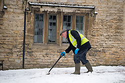 © Licensed to London News Pictures. 28/12/2020. Burford, UK. A man clears snow from the pavement in front of a residential property in the village of Burford in Oxfordshire, south England as the UK experiences freezing temperatures over night. Photo credit: Ben Cawthra/LNP