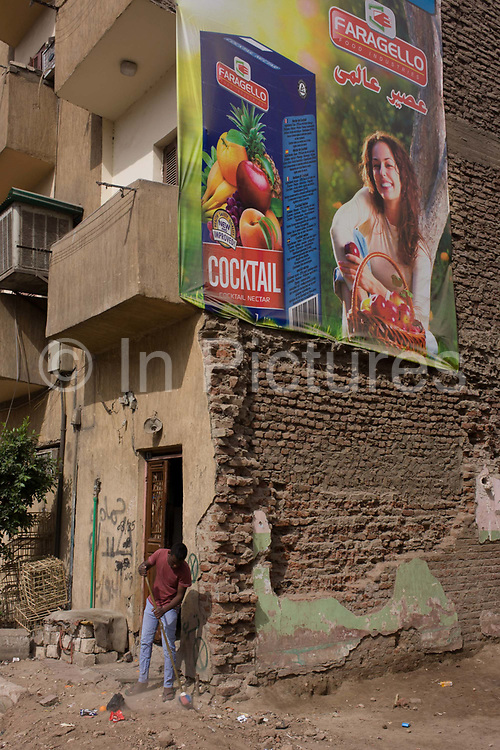 A local man sweeps away dust beneath a poster for healthy living with wasteground dereliction in Luxor, Nile Valley, Egypt. The Faragalla group was founded in 1973 by Eng. Mohamed Farag Amer and produce over one thousand different products in the field of processed meat and chicken, frozen vegetables & fruits, concentrated fruit juices and pulp, packed fruit juices in glass and tetrapak, confectioneries, bakeries, tomato paste , jams, processed cheese, chicken stock and instant juice powder etc. The group is considered to be one of the biggest and most diversified food companies in the Middle East, exporting to more than 130 countries all over the world including USA, Western Europe, Middle east and Africa.
