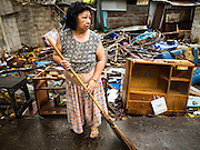 28 SEPTEMBER 2015 - BANGKOK, THAILAND: A woman who lives in the Wat Kalayanamit neighborhood sweeps the sidewalk in front of a destroyed home. Fifty-four homes around Wat Kalayanamit, a historic Buddhist temple on the Chao Phraya River in the Thonburi section of Bangkok, are being razed and the residents evicted to make way for new development at the temple. The abbot of the temple said he was evicting the residents, who have lived on the temple grounds for generations, because their homes are unsafe and because he wants to improve the temple grounds. The evictions are a part of a Bangkok trend, especially along the Chao Phraya River and BTS light rail lines. Low income people are being evicted from their long time homes to make way for urban renewal.    PHOTO BY JACK KURTZ