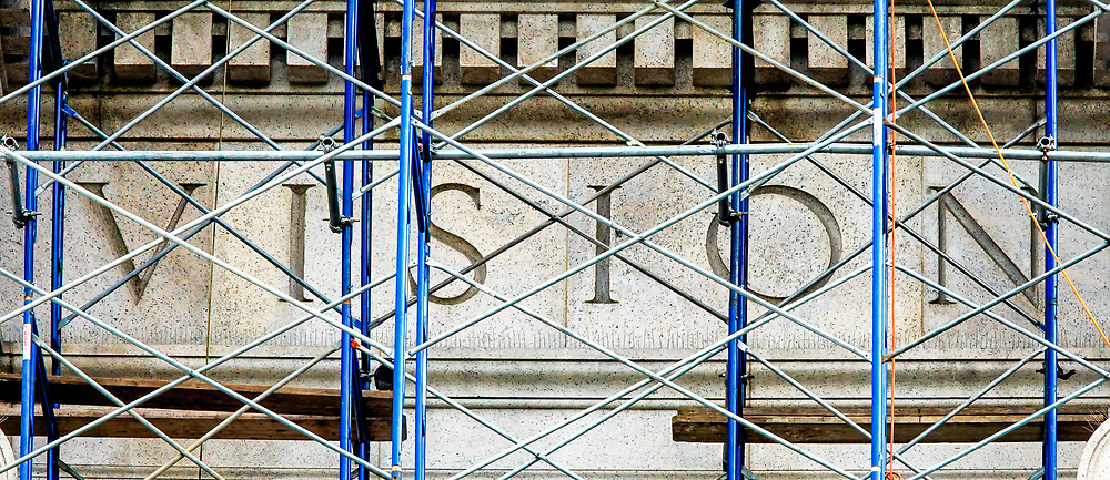 Vision: Not unlike the normal re-evaluation of a personal perception or understanding; the word Vision is seen through the metal scaffolding during the extensive renovations of the frontal fascia of the Museum of Natural History, New York, New York United States of America.