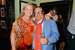 Australian TV personality LYNDEY MILAN and LAURENCE ISAACSON at a Bastille Day Cocktail Party at L'Escargot, 48 Greek Street, London on 14th July 2014.