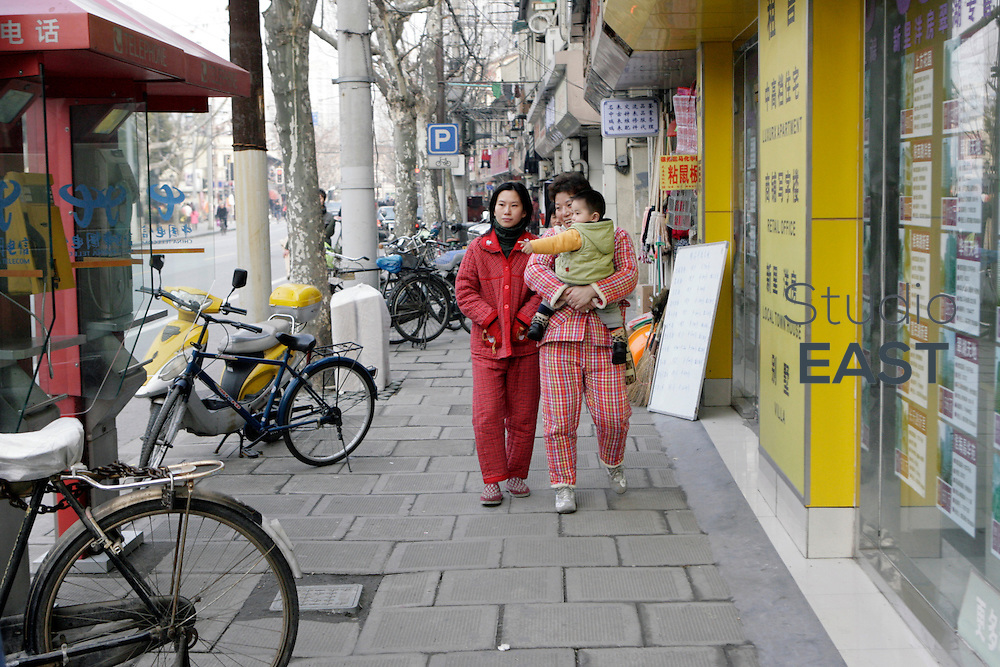 Shanghai, China - January 08: Two women in their pyjamas walk a baby on January 8, 2009 in Shanghai, China. (Photo by Lucas Schifres/Getty Images)