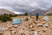 A backpacker walks through camp above Vidette Meadow; John Muir Trail/Pacific Crest Trail; Sequoia Kings Canyon Wilderness; Kings Canyon National Park; Sierra Nevada Mountains, California, USA.