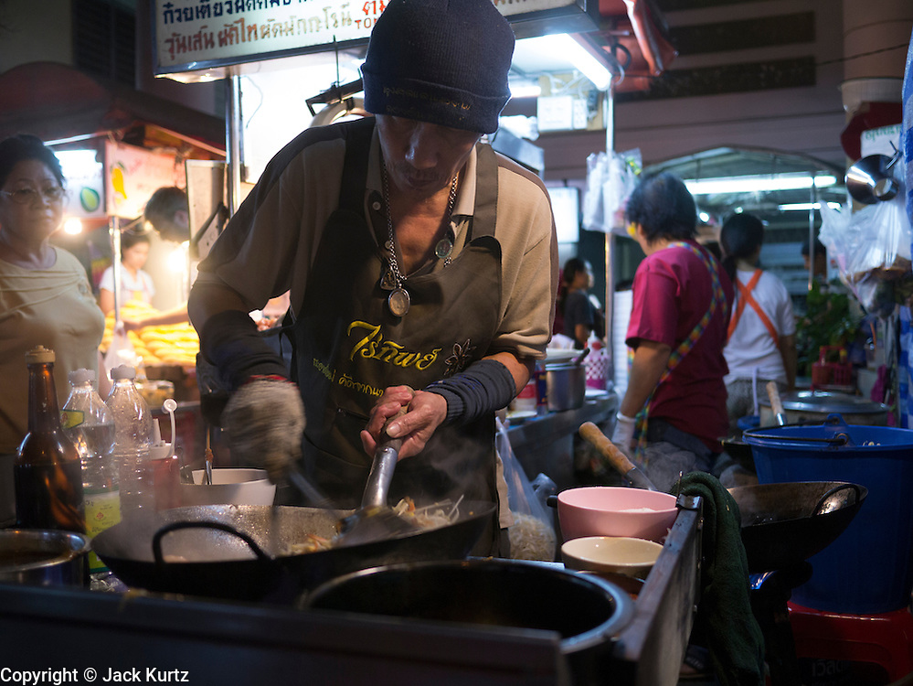 05 JANUARY 2013 - BANGKOK, THAILAND:  A food vendor cooks a meal in his street food stand on Skhumvit Soi 38. Sukhumvit Soi 38, near the Thong Lor BTS Station, is generally considered one of the best street food areas in Bangkok. Most of the food stalls are only open in the evening and they are usually crowded with both Thais and foreign tourists.   PHOTO BY JACK KURTZ