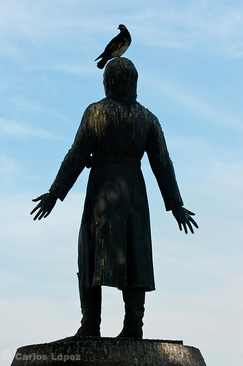 """A dirty statue of the priest of """"dolores"""" ( cura de dolores ), Don Miguel Hidalgo y Costilla with a pigeon on top of his head in the city of Manzanillo of the state of Colima in Mexico."""