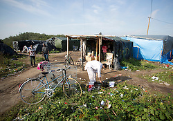 """© Licensed to London News Pictures. 30/08/2015. Calais, France. A bike is parked outside one of the shops at the camp, also known as the Jungle, at Calais, France. Today around a hundred British cyclists from """"Critical mass to Calais"""" arrived at the refugee camp in a two-day ride from London to donate bicycles and supplies to support the life at the site. Photo credit : Isabel Infantes/LNP"""