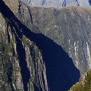 A tourist cruise ship dwarfed by the steep cliff faces of Milford Sound, South Island, New Zealand. .Milford Sound (Piopiotahi in Ma¯ori) is a fjord in the south west of New Zealand's South Island, within Fiordland National Park and the Te Wahipounamu World Heritage site. It has been judged the world's top travel destination and is acclaimed as New Zealand's most famous tourist destination..Milford Sound runs 15 kilometres inland from the Tasman Sea at Dale Point - the mouth of the fiord - and is surrounded by sheer rock faces that rise 1,200metres (3,900ft) or more on either side. Among the peaks are The Elephant at 1,517metres (4,977ft), said to resemble an elephant's head and The Lion, 1,302metres (4,272ft), in the shape of a crouching lion. Lush rain forests cling precariously to these cliffs, while seals, penguins, and dolphins frequent the waters and whales can be seen sometimes..Milford Sound sports two permanent waterfalls all year round, Lady Bowen Falls and Stirling Falls. After heavy rain many hundreds of temporary waterfalls can be seen running down the steep sided rock faces. .The beauty of this landscape draws thousands of visitors each day, with between 550,000 and 1 million visitors in total per year. This makes the sound one of New Zealand's most-visited tourist spots, and also the most famous New Zealand tourist destination.  Milford Sound, New Zealand. 29th April 2011. Photo Tim Clayton