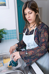 Woman washing dishes at the kitchen sink,