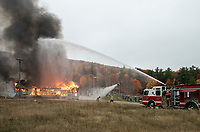 Members of the Gunstock snowmaking crew and Gilford Fire assist to control the burning of the Phelps Barn Saturday afternoon following a series of fire fighting training sessions.  (Karen Bobotas Photo/for The Laconia Daily Sun)