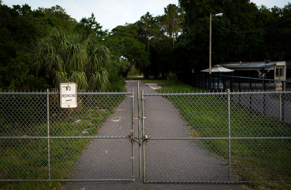 A gate blocks a service road leading to Sawgrass Lake Park neighboring the Skyway Trap & Skeet and Club on April 12, 2016 in St. Petersburg, Fla. In 2004, the Southwest Florida Water Management District spent $25 million in taxpayer money to remediate toxic lead from the wetlands and build a berm to stop further contamination. After a decade-long legal battle between the District and the gun range, a lawsuit was dropped in February after NRA lobbyist Marion Hammer called for the agency's dissolution. (David Albers for The Trace)