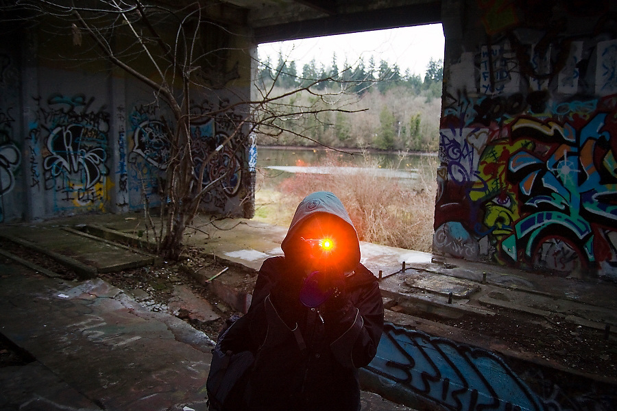 A young woman takes a picture in an abandoned warehouse in Blakely Harbor Park on Bainbridge Island, Washington. The park is the former site of Port Blakely Mill, one of the world's largest sawmills in the late 19th century.