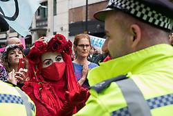 London, UK. 23rd August, 2021. A member of the Extinction Rebellion Red Rebel Brigade looks at a Metropolitan Police officer during the first day of Impossible Rebellion protests in the Covent Garden area. Extinction Rebellion are calling on the UK government to cease all new fossil fuel investment with immediate effect. Credit: Mark Kerrison/Alamy Live News