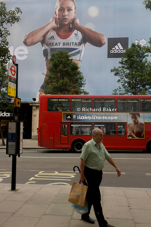 A man walks near the inspiring image of Team GB gold medallist heptathlete Jessica Ennis and diver Tom Daley which adorns the exterior of the Adidas store in central London's Oxford Street, during the London 2012 Olympic Games. The ad is for sports footwear brand Adidas and their 'Take The Stage' campaign which is viewable across Britain and to Britons who have been cheering these athletes who have been winning medals in numbers not seen for 100 years. Their heroic performances have surprised a host nation who until the victories, were largely anti-Olympics - now adoring their darling Ennis and her good looks.