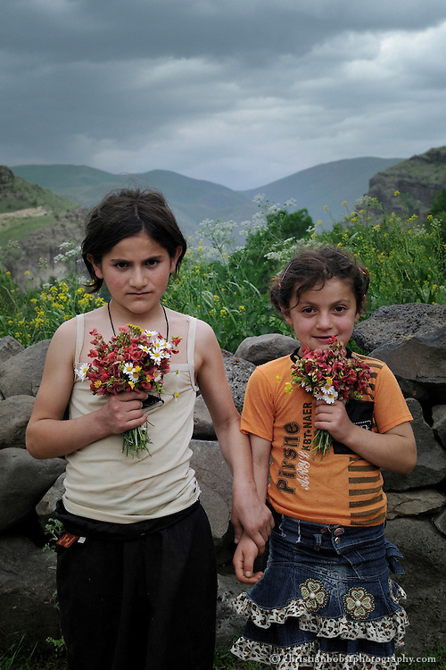 Portrait of two sisters with flowers who live in in Mirashkhani, Georgia. Photographed for HEKS, a Swiss NGO.