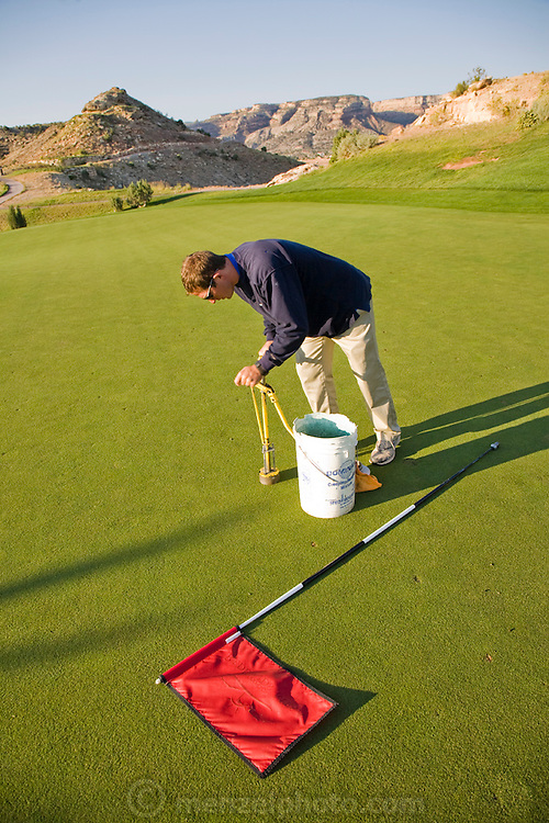 Bob Sorensen, an assistant golf course superintendent of The Golf Club at Redlands Mesa in Grand Junction, Colorado moves a putting hole during an early morning inspection of the golf course. (Bob Sorensen is featured in the book What I Eat: Around the World in 80 Diets.) He played football at Mesa State College in Grand Junction and graduated with a degree in criminal justice. Just before he took a desk job in his chosen profession he decided that he didn't want a desk job and found one that requires his constant attendance of the great outdoors, at a golf course at the foot of the majestic Colorado National Monument.  He earned a second degree in turf management, supervises a small crew of greenskeepers, and coaches high school football at Palisade High School.