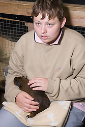 Young woman with learning disabilities on a trip to an animal centre stroking a pet guinea pig,