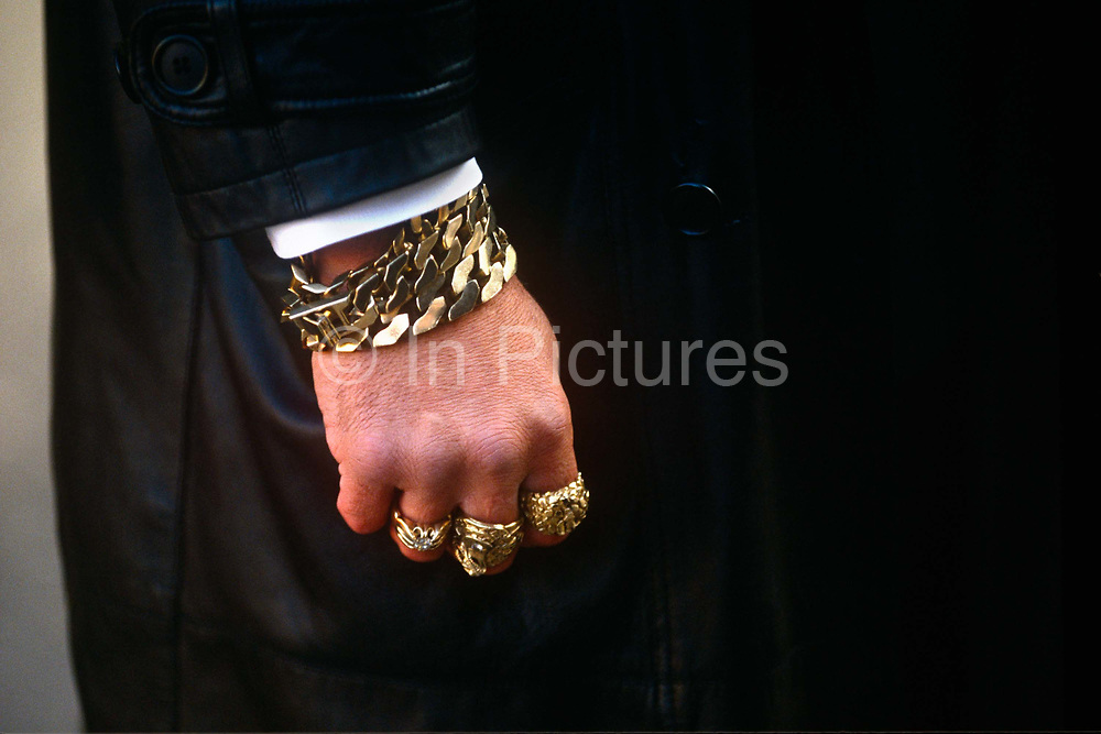 A detail of a fist adorned with gold rings, a bracelet and bling of a gangster family security man during the East End funeral to notorious criminal twin Ronnie Kray. The anonymous man is only seen from is lowered hand and the man who wears a black leather coat. He stands guard before the Kray coffin appears from the Bethnal Green undertakers. Ronald, commonly referred to as Ron or Ronnie suffered from paranoid schizophrenia while he and his twin brother Reggie were involved in armed robberies, arson, protection rackets and violent assaults including torture during the 1950s and 60s. They terrorised their organised crime competitors but were loved by the communities of East London. The Kray gangster twins were eventually jailed separately in 1969 and Ronnie remained in Broadmoor (psychiatric) Hospital until his death on 17 March 1995.