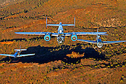"""An air to air color photographic image of three classic World War II 'planes (B-25 Mitchell """"Maid in the Shade"""", P-51 Mustang """"Cripes A' Mighty"""" and a TBM-3 Avenger) flying over Red Mountains in the Arizona desert"""