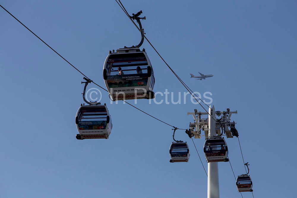 Emirates Air Line cable cars travel across the River Thames between Greenwich Peninsula and the Royal Docks in London, England, United Kingdom.  A BA 747 Aeroplane passes by in the sky.  The Air Line opened in 2012  and was built by Doppelmayr with sponsorship from the airline Emirates.