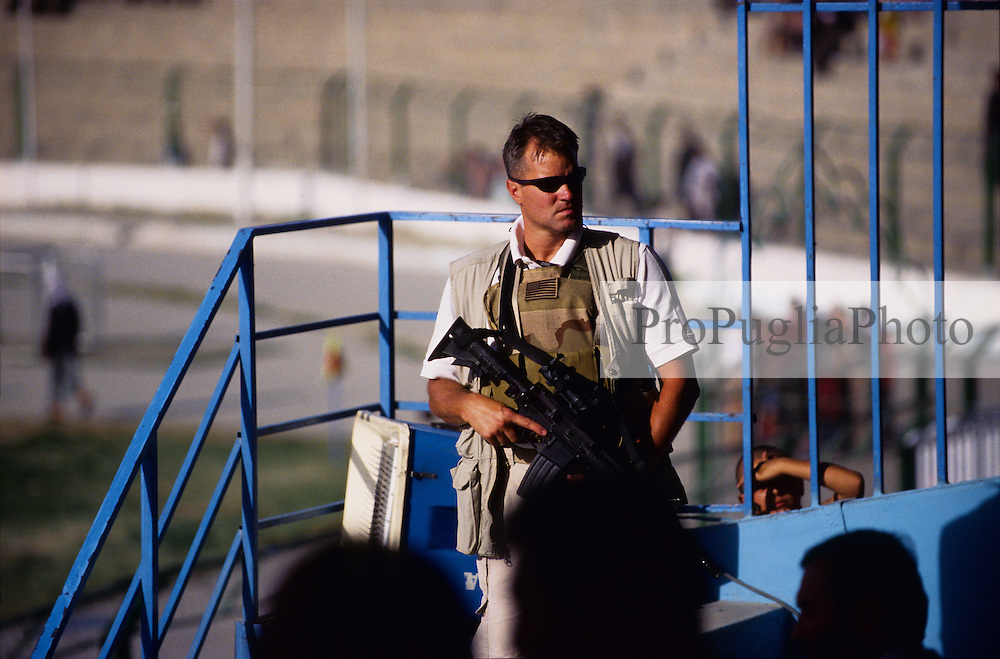 SPECIAL OLYMPICS AFGHANISTAN 2005..Kabul, 23 August 2005..U.S. Army officer stands at Ghazi Stadium as the special guests, including the new appointed US Ambassador to Afghanistan, arrive for the  Olympics opening...On 23-25 August 2005, Special Olympics Afghanistan held its first national Games at Olympic Stadium in Kabul...More than 300 athletes, including 80 female athletes, experienced a taste of happiness and achievement for the first time in their lives. They competed in athletics, bocce and football (soccer). Because of cultural restrictions, males and females competed at separate venues.
