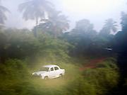 Ambassodor car driving through lush landscape.Misted effect. Cochin, Kerala, India