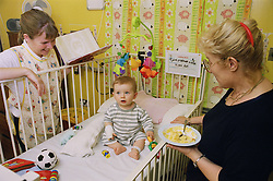 Grandmother feeding baby sat in cot on Children's renal ward,