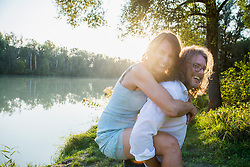 Couple enjoying piggyback by river, Bavaria, Germany