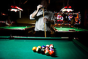 A patron applies chalk to his pool cue at the start of a new round of 8-ball at the Knarr Tavern in Seattle, Washington.