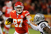 Kansas City Chiefs tight end Travis Kelce (87) runs for a first down after catching a Patrick Mahomes pass as Oakland Raiders cornerback Nick Nelson (23) defends during the third quarter of an NFL football game against the Oakland Raiders in Kansas City, Mo., Sunday, Dec. 30, 2018.   (AP Photo/Colin E. Braley)