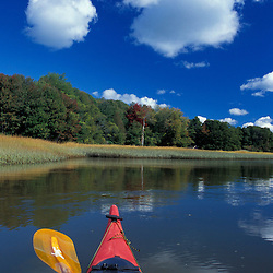 Yarmouth, ME. The bow of a kayak in the Royal River.  Salt Marsh.  Puffy cumulus clouds. TPL project.