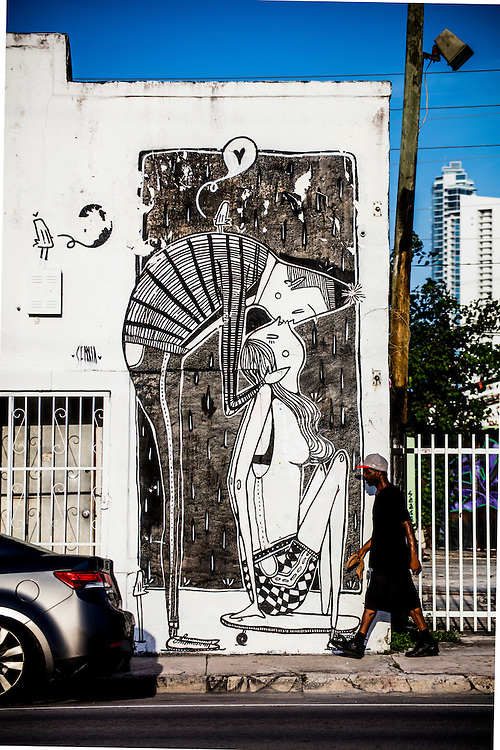 In Miami's Wynwood district, famous for its street art, a man strides by a mural of a couple kissing.