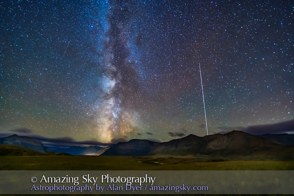 The northern summer Milky Way setting over the mountains of Waterton Lakes National Park, Alberta, Canada, with the Space Station rising at right, then fading into sunset, in a trail from the series of long exposures. This is from the Bison Compound viewpoint looking south and southwest, on September 21, 2019, in frames taken as part of a time-lapse. <br /> <br /> This is a stack of 8 images for the ground to smooth noise, one image from the set for the stars to minimize trailing, and a stack of 6 images masked to reveal just the ISS trail. The trail fades to deep red as the ISS travels into the Earth's shadow as it rose here and experienced sunset at their altitude. A mild Orton glow effect added with Luminar Flex. <br /> <br /> Each exposure in the set was 30 seconds at ISO 4000 and f/2 with the Venus Optics 15mm lens and Sony a7III. Part of a 360-frame time-lapse.