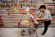 (MODEL RELEASED IMAGE). Craig Caven takes a moment to ponder his family's weekly grocery list in one of the aisles of Raley's, a California grocery chain. (Supporting image from the project Hungry Planet: What the World Eats.) The Caven family of American Canyon, California, is one of the thirty families featured, with a weeks' worth of food, in the book Hungry Planet: What the World Eats.