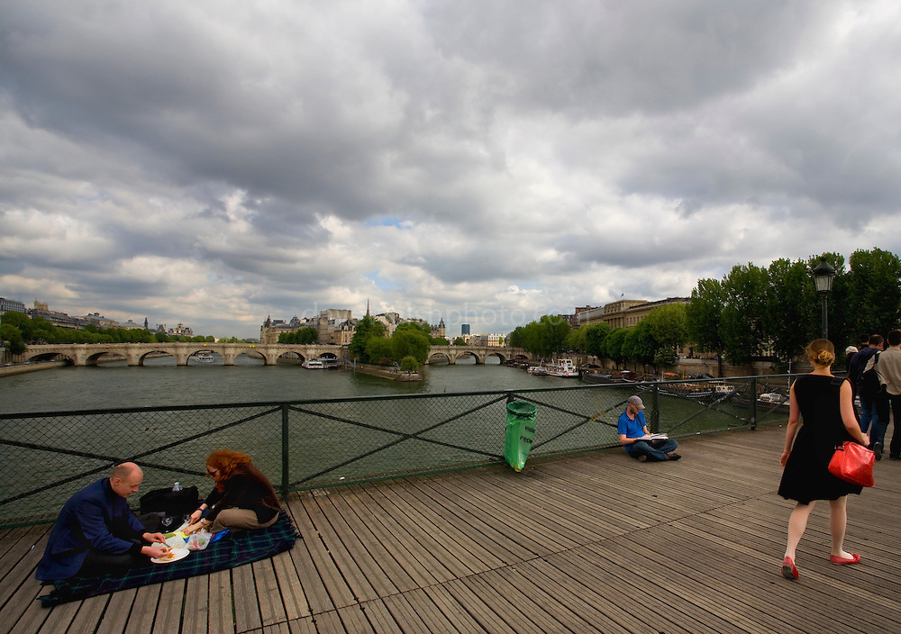 Couple having a picnic on the Pont des Arts, footbridge over the Seine river, Paris, France. But who is the girl in the red shoes?