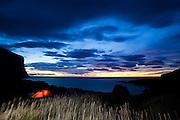 A tent glows at dusk on Horseid Beach, Moskensoya, Lofoten Islands, Norway.