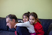 """Father Eduard Polanski (47) is playing with his daughters Sara (6) on the right and Kristina (4) in their temporary home in Ostrava. Sara's mother was advised from one of the schools that she should not enrol her daughter there - after the girl passed the enrolment test - because Sara is so """"slim"""". Mother Ingrid Kandracova (36) new that the final decision is on her side and she refused the advice and enrolled her daughter in the school."""