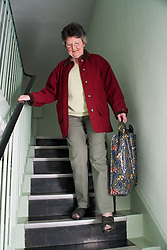 Woman walking down stairs with a shopping bag,