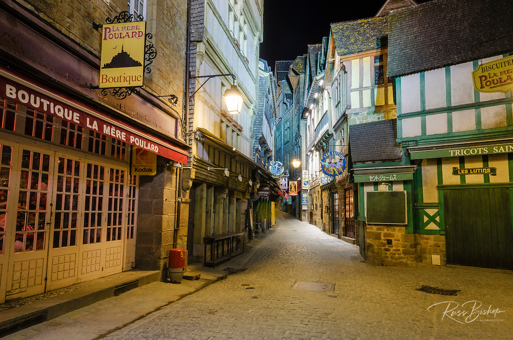 Shops and cobblestone street at night, Mont Saint-Michel, Normandy, France