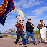 Jay Chee, right, Edmund Yazzie and William Skeet lead other protestors on a march to the Navajo Nation Council Chambers in Window Rock Monday.