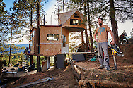 A young man proudly stands with a chainsaw in front of his handmade treehouse constructed entirely out of reclaimed materials near Wenatchee, Washington.