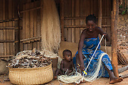 Sakalava woman working with Raffia from the Raffia palm (Raffia rarinifera) The fibres are combed out from the leaves once the leaves have dried.  They are either left their natural colour or dyed with various natural dyes. These are then woven into hats, baskets and mats that are very characteristic of Madagascar. There is a project in the Ankarafantsika Nature Reserve helping several local communities to sustainably yield the palm leaves and thereby make a living from the forest and earn money rather than live off the forest causing more habitat distruction.<br /> Ankarafantsika Nature Reserve, Western deciduous forest. MADAGASCAR