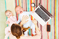 Mother with Twin Babies Lying on Floor Using Laptop, Elevated view