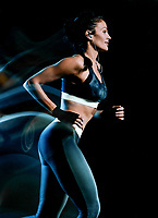 one beautiful caucasian mixed race woman unner jogger jogging running  in studio isolated on black background