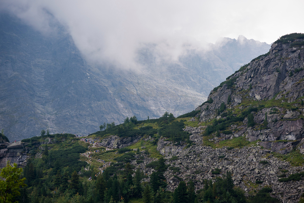 As bad weather moves in, a line of people hike on a trail connecting two lakes, Morskie Oko and Czarny Staw, in the Tatra National Park in southern Poland.