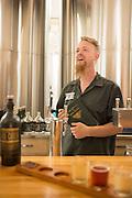 "Nat West of Reverend Nat's Cidery in Portland, Oregon holds one of his cider ""bibles"" reverently."