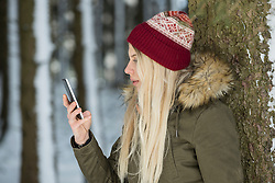 Teenage girl reading message on mobile phone in forest, Bavaria, Germany