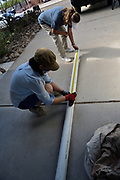 Sarah and Mara measure plumbing pipe before cutting it to fit.