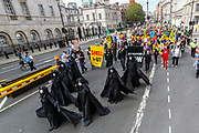 People some of them wearing face masks, hold placards and banners as they march along seven 'Oil Slicks' activists dressed in black-clads on a march against 'ecocide' seeking to step up pressure on Shell and demand an end on fossil fuel extraction. Earlier on Tuesday, Sept 8, 2020 - Extinction Rebellion activists staged a performative protest enacting a crime scene outside Shell Headquarters in Jubilee Gardens, central London. Environmental nonviolent activists group Extinction Rebellion enters its 8th day of continuous ten days protests to disrupt political institutions throughout peaceful actions swarming central London into a standoff, demanding that central government obeys and delivers Climate Emergency bill. (VXP Photo/ Vudi Xhymshiti)