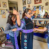 Miss Zuni Tyra Quetawki raises her arms as mother Michele, left, and her aunt Valerie Martinez  help dress her at their home in Zuni Wednesday.